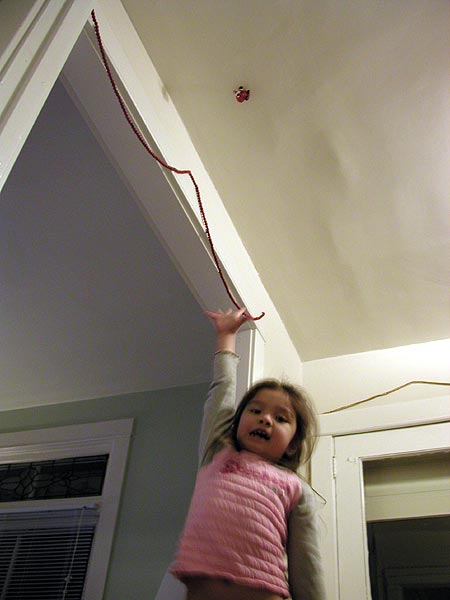 reaching for the santa that's stuck to the ceiling
