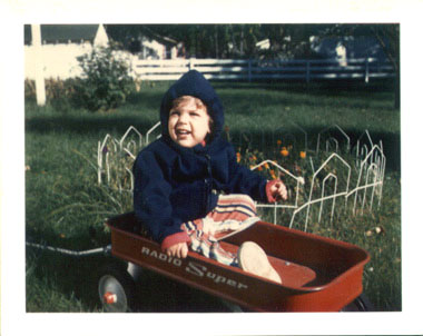 toddler Tommy wearing a hooded sweatshirt while sitting in a red Radio Flyer wagon in the backyard