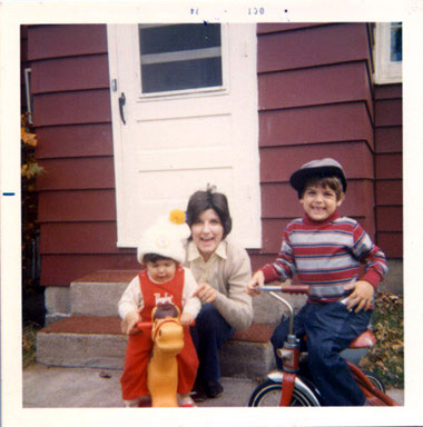 young Tom hanging out on the back steps on his tricycle while baby Sharyn is perched on a plastic rocking horse