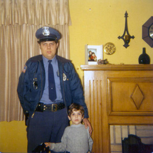 Dad in his police uniform posing with Tommy by the fireplace
