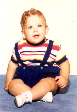 photo of a very chubby Tommy around his first birthday, posed, wearing overall shorts with a striped shirt